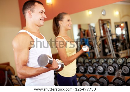 Portrait of young man training in gym with pretty girl near by