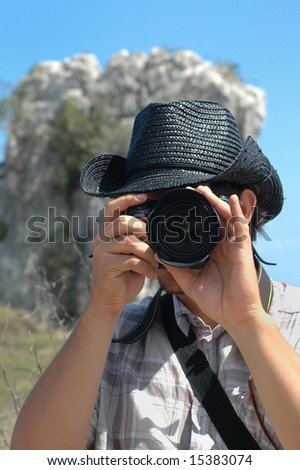 Portrait of young man using professional camera in nature background