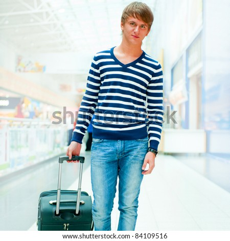 Portrait of young man walking inside modern airport with trolley bag wearing stylish casual clothes