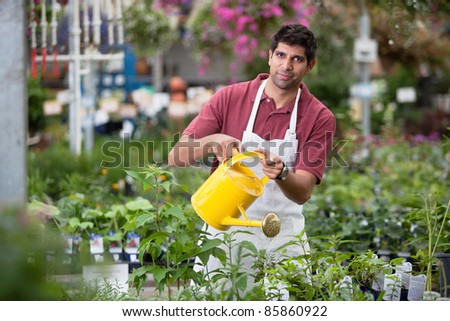 Portrait of young man watering the plants
