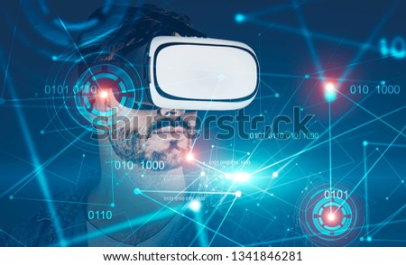 Portrait of young man wearing jeans shirt and VR glasses with double exposure of HUD and immersive binary interface. Toned image #1341846281