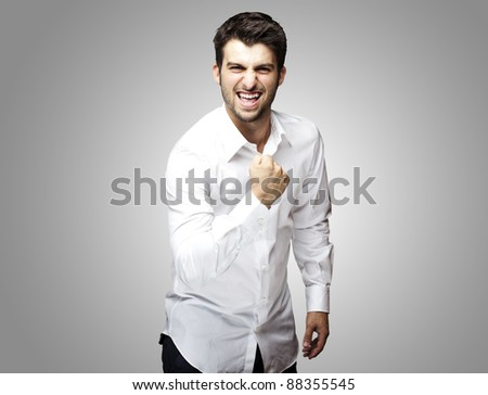 portrait of young man winner gesture against a grey background