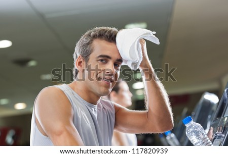 Portrait of young man wiping sweat with towel at health club