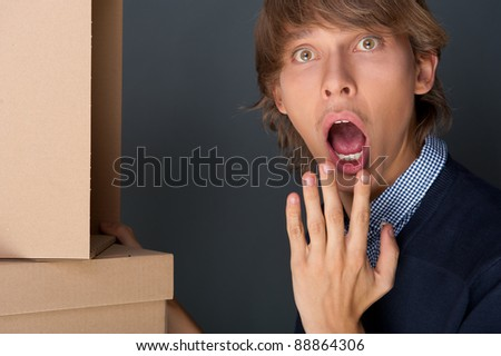 Portrait of young man with boxes against grey wall. He is afraid of starting new life