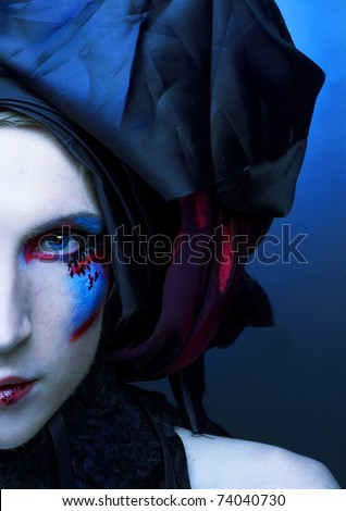 Portrait of young man with creative make-up in black and red turban