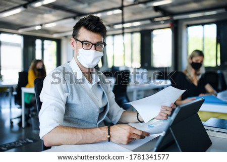Portrait of young man with face mask back at work in office after lockdown.