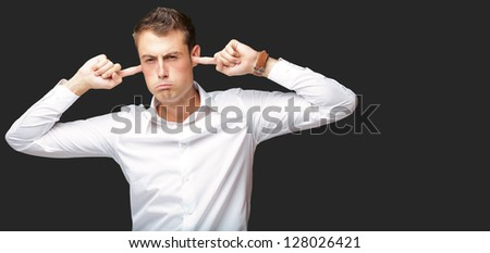 Portrait Of Young Man With Finger In His Ear On Black Background - stock photo