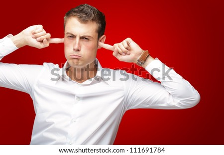 Portrait Of Young Man With Finger In His Ear On Red Background