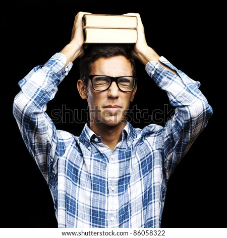 portrait of young man with glasses holding books on his head over black background
