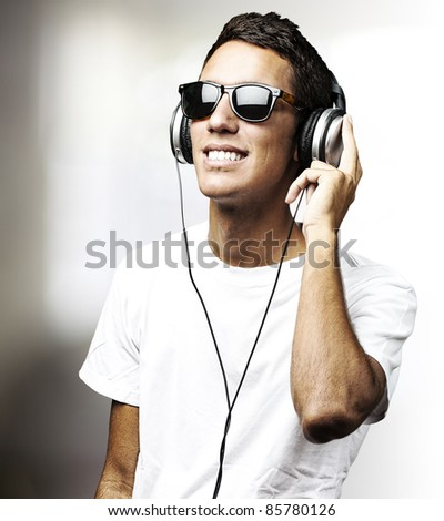 portrait of young man with glasses listen to music in a living room