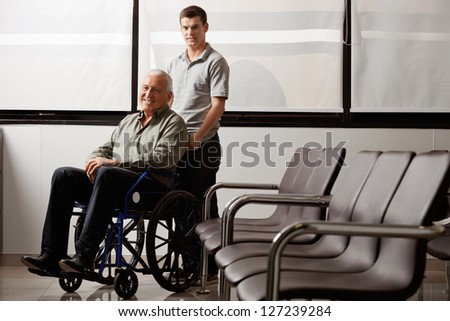 Portrait of young man with his grandfather on wheelchair in hospital lobby