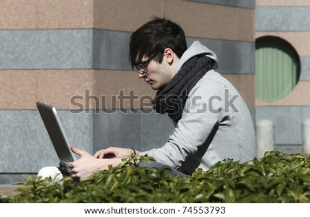 portrait of young man with his laptop, outdoors