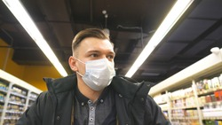Portrait of young man with medical face mask walking at supermarket. Guy going at shop with protective mask from virus. Shopping in the grocery during coronavirus pandemic. Concept of health. COVID-19