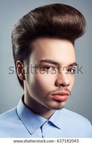 Portrait of young man with retro classic pompadour hairstyle. studio shot. looking at camera.