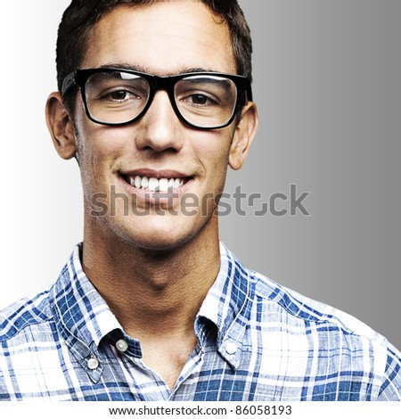 portrait of young man with shirt and glasses over a grey background
