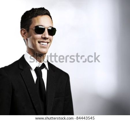 portrait of young man with suit and sunglasses in a house