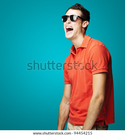 portrait of young man with sunglasses laughing over blue background
