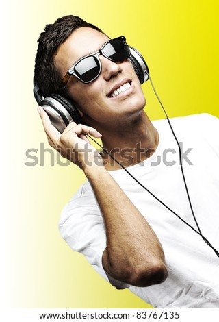 portrait of young man with sunglasses playing to music on a white background