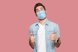 Portrait of young man with surgical medical mask in blue casual style shirt standing, thumbs up and looking at camera with surprised happy face. indoor studio shot, isolated on pink background.