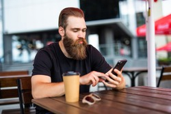 Portrait of young man with the beard texting message into his workgroup using the smartphone while waiting for a food order in street restaurant