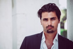 Portrait of young man with trendy style. Trendy hair and goatee. He wears a white shirt and jacket.