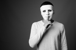 Portrait of young man with white mask against gray background