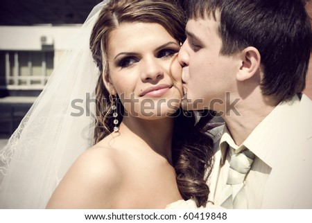 Portrait of young married couple sitting on bench #60419848