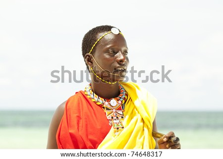 Portrait of young Massai man posing on beach; portrait with narrow focus