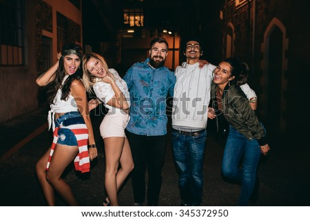 Portrait of young men and women looking at camera laughing. Multiracial group of young friends hanging out in outdoor party.