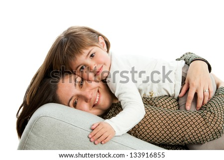 Portrait of young mother with daughter on couch.Isolated.