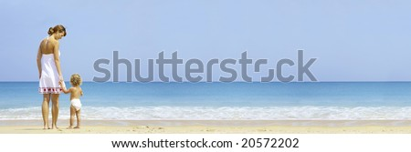 Portrait of young mother with her baby  having fun on the beach