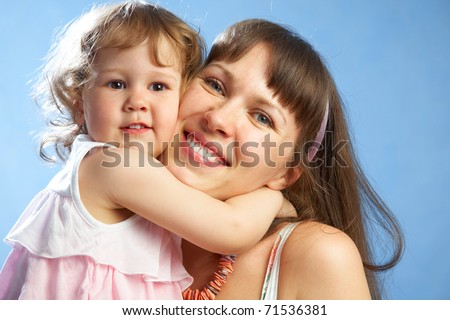 Portrait of young mother with her daughter on the blue background