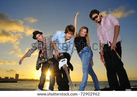 Portrait of young musical band posing outdoors at sunset with instruments - stock photo