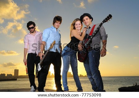 Portrait of young musical band with 3 boys and a girl posing outdoors at sunset with instruments