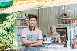 portrait of young muslim men and women selling food and drinks using container