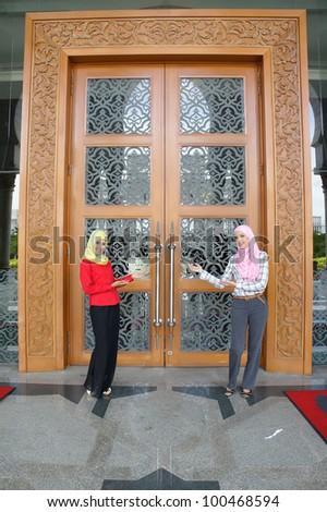 Portrait of  young muslim woman standing in front of door welcoming guest
