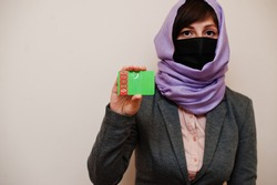 Portrait of young muslim woman wearing formal wear, protect face mask and hijab head scarf, hold Turkmenistan flag card against isolated background. Coronavirus country concept.