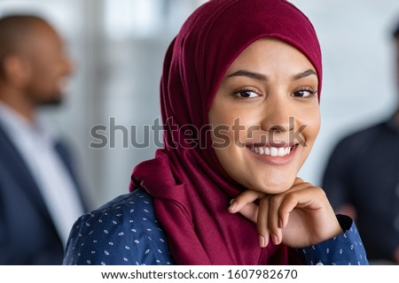 Portrait of young muslim woman wearing hijab in office while looking at camera. Close up face of arabic business woman covered with headscarf smiling. Successful arab businesswoman in modern office. Stock fotó ©