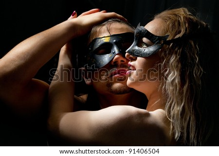 Portrait of young mysterious couple in a Venetian mask during sexual foreplay