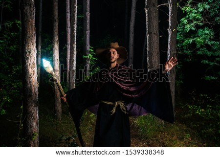 Portrait of young mysterious wizard having fun into the woods