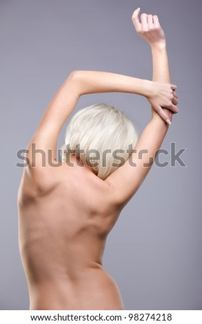 portrait of young naked blonde woman with beautiful body posing back to camera - stock photo