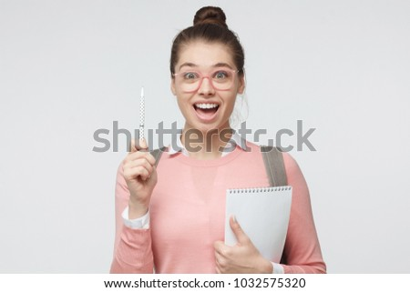 Portrait of young naturally looking female isolated on gray background showing eureka sign with her pen to indicate significant information with smile and eyes wide open