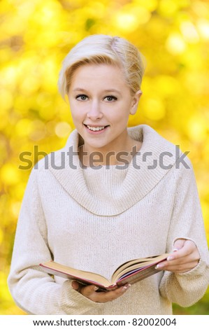 Portrait of young nice blond woman wearing beige pullover and holding a book at autumn park.
