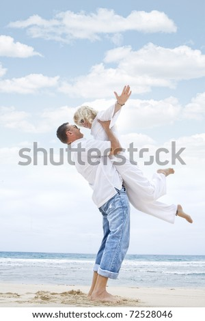 Portrait of young nice couple having good time on the beach