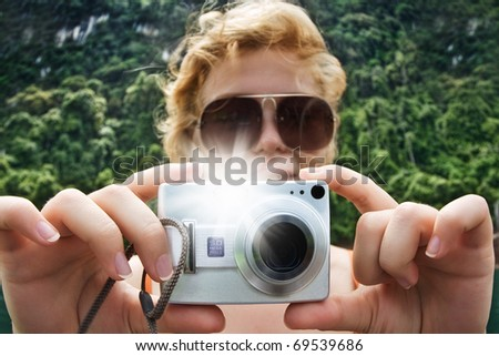 Portrait of young nice woman taking photo in summer environment