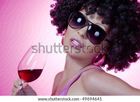 Portrait of young nice woman with glass of wine on pink back