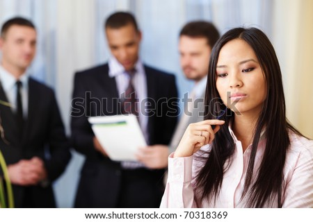 Portrait of young pensive asian woman with her business partners on the background