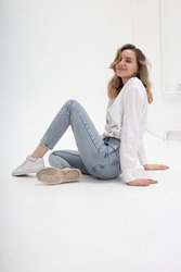 portrait of young pensive caucasian woman posing in shirt and blue jeans, sitting on white studio floor. model tests of pretty girl in basic clothes on cyclorama. attractive female poses, model tests