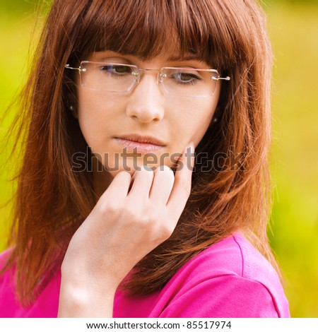 Portrait of young pensive woman in pink blouse wearing eyeglasses standing at park and looking somewhere.