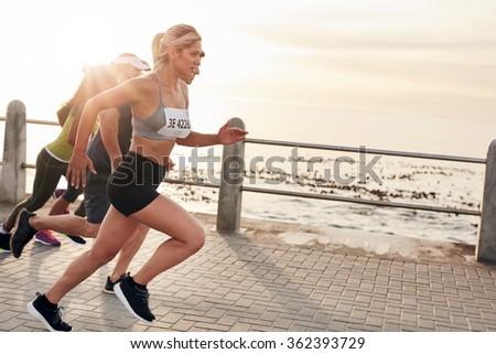 Portrait of young people running on seaside promenade. Group of women running marathon. #362393729